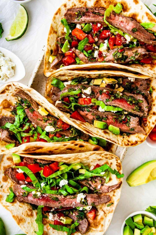 overhead shot of steak tacos on a platter with chimichurri sauce and garnished with tomatoes, avocado and feta