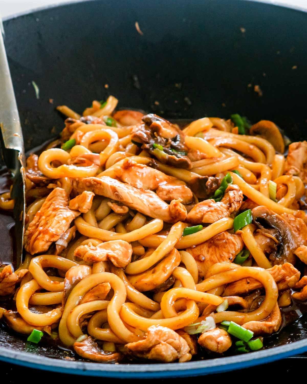 sideview shot of hoisin chicken udon noodles in a blue wok