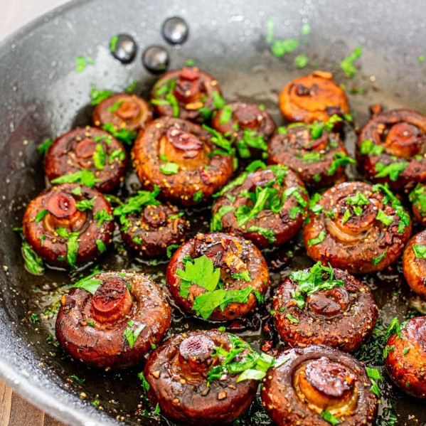 red wine garlic mushrooms in a skillet topped with chopped parsley