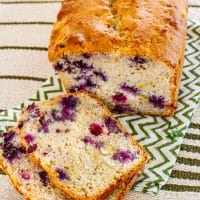a loaf of banana blueberry bread with two slices sitting in front of it