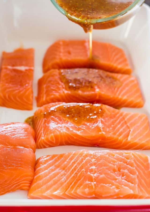 pouring maple mustard glaze on salmon fillets in a baking dish