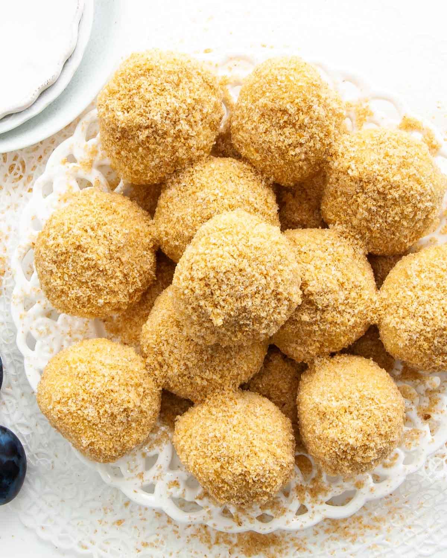 overhead shot of plum dumplings on a white dessert plate