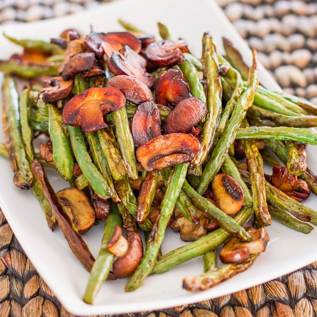 a white plate with roasted green beans and mushrooms