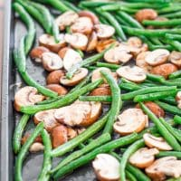 green beans and mushrooms on a baking sheet ready to be roasted on a