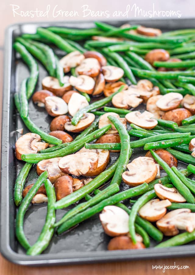 a baking sheet filled with green beans and cremini mushrooms