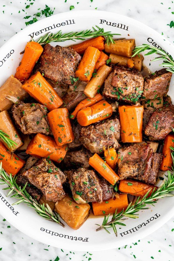 a bowl full of slow cooker short ribs and carrots surrounded by sprigs of rosemary