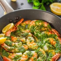 a skillet full of garlic parsley butter shrimp garnished with lemon wedges