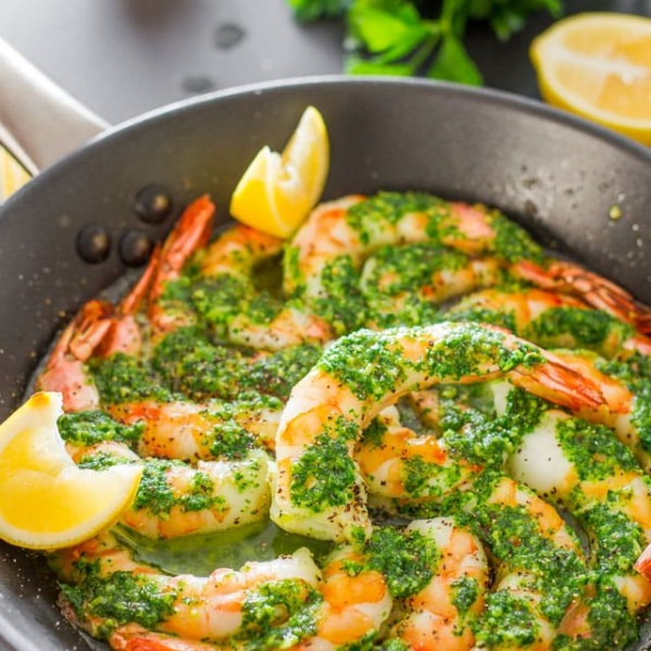 a skillet full of garlic and parsley butter shrimp garnished with lemon wedges
