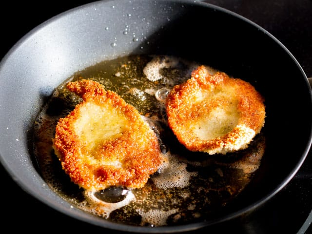 pork schnitzel frying in a skillet