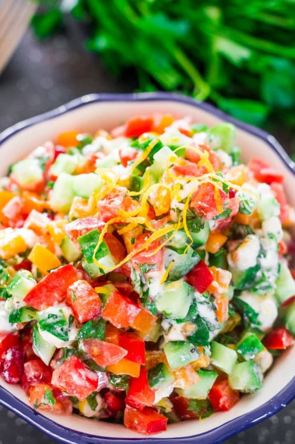 a bowl full of israeli salad with goat cheese