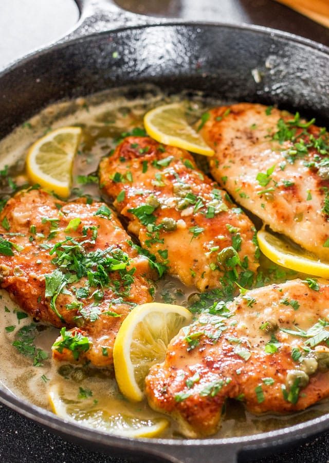 Lemon Chicken Piccata in a skillet with lemon slices and parsley.