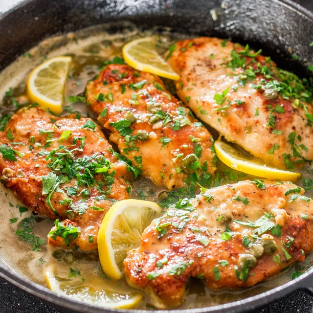 lemon chicken piccata in a skillet with lemon slices and parsley