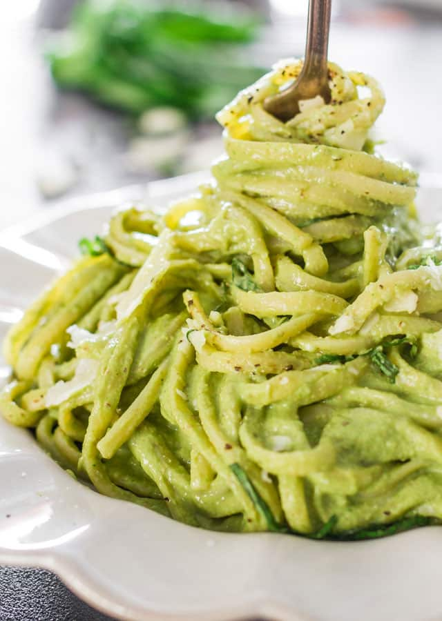 a fork twirling avocado and spinach pasta in a plate