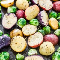 raw potatoes and brussels sprouts on a baking sheet