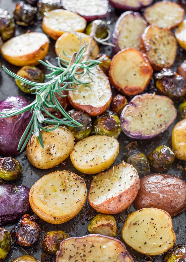 Close up shot of Rosemary Balsamic Baby Potatoes and Brussels Sprouts with a sprig of rosemary as garnish