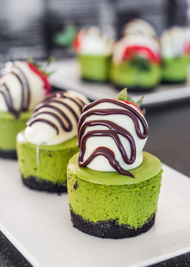 3 Matcha Mini Cheesecakes topped with white chocolate strawberries on a white plate