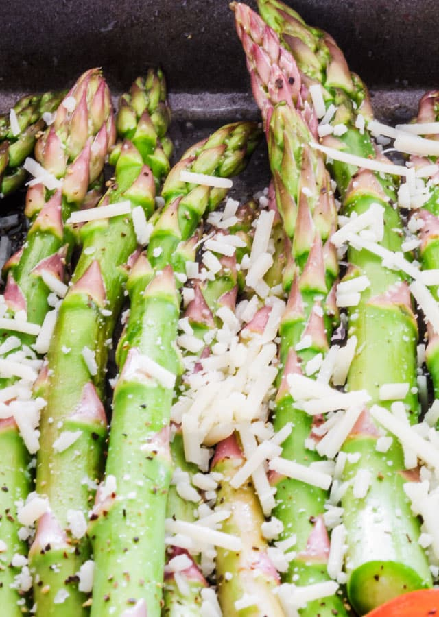 uncooked asparagus topped with shredded cheese
