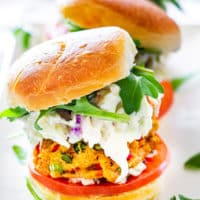 3 crab cake sliders on a white plate garnished with baby arugula