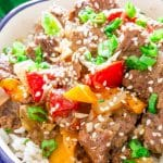 a bowl full of rice topped with slow cooker beef and bell peppers