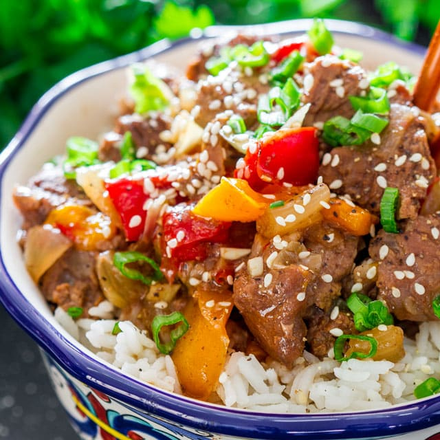 close up of Slow Cooker Pepper Steak served in a bowl over rice