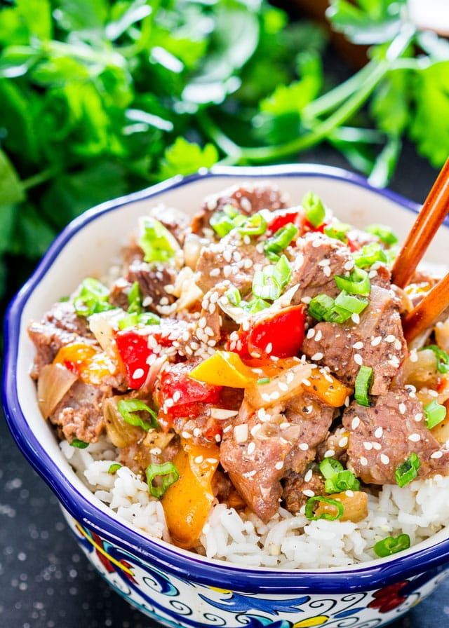 Slow Cooker Pepper Steak served in a bowl over rice
