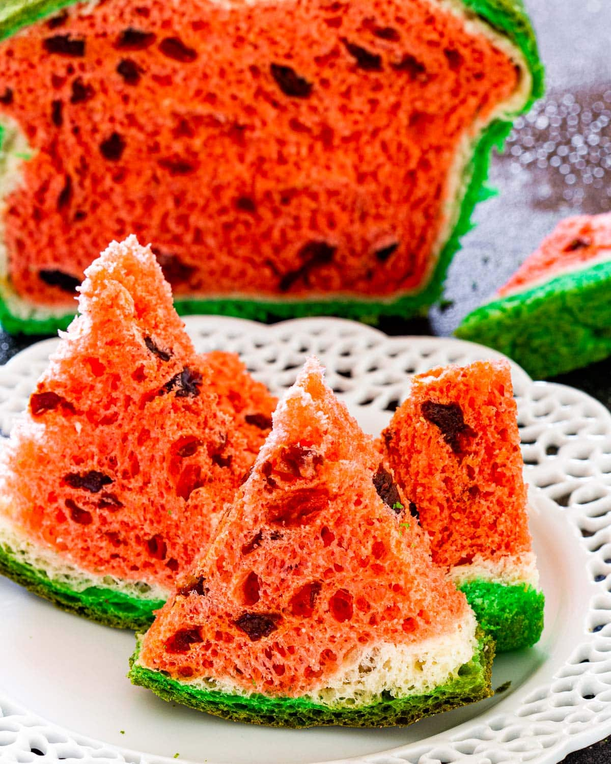 3 wedges of watermelon look-alike bread on a white bread with the bread in the background