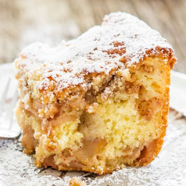 a slice of apple pie cake dusted with powdered sugar on a plate