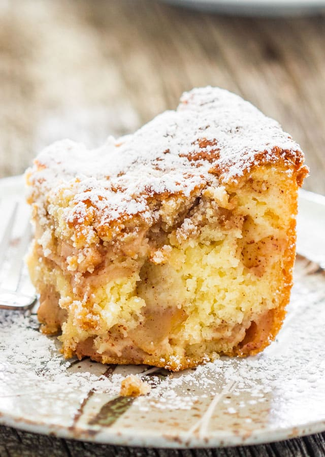slice of Apple Pie Cake on a plate sprinkled with powdered sugar