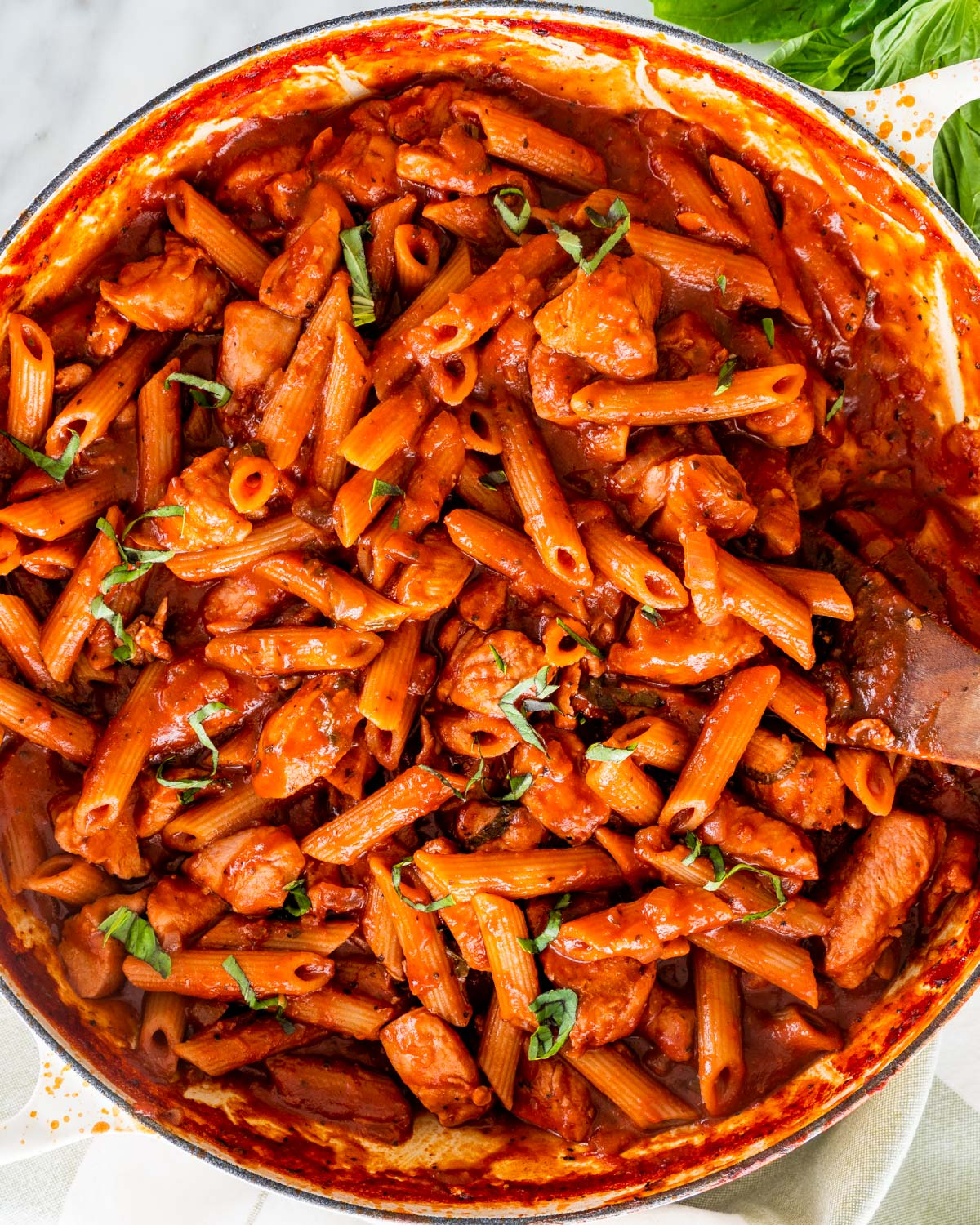 overhead shot of chicken penne arrabbiata in a dutch oven braiser garnished with basil and a wooden spoon inside