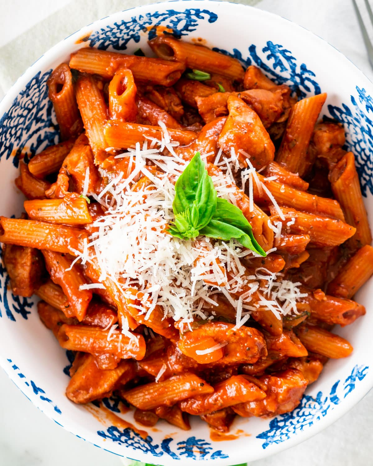 overhead shot of a portion of chicken penne arrabbiata in a white and blue plate garnished with a bit of parmesan cheese and a couple basil leaves