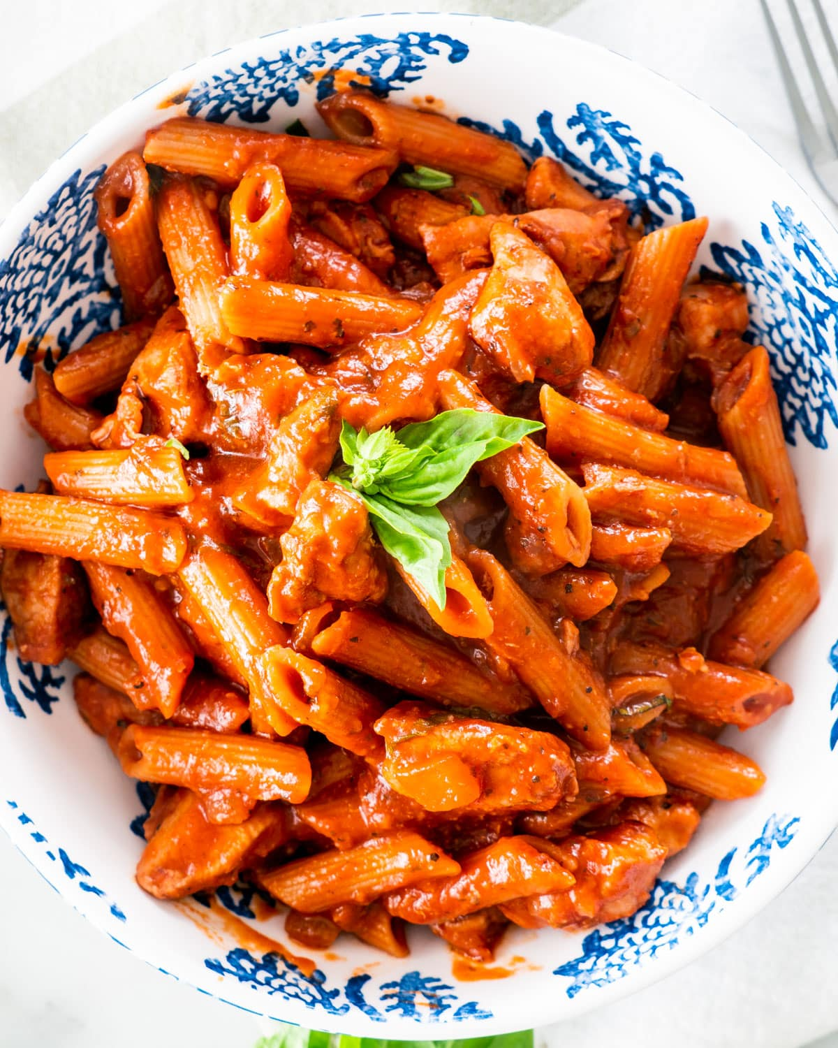 overhead shot of a portion of chicken penne arrabbiata in a white and blue plate garnished with a couple basil leaves