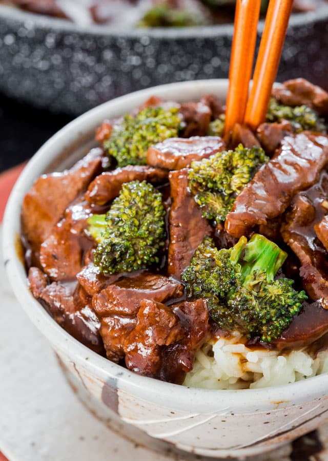 beef and broccoli on a bed of rice in a bowl