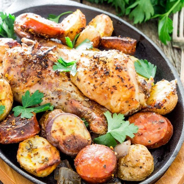 a skillet full of spanish chicken with chorizo and potatoes