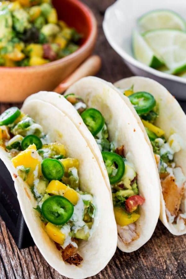 three blackened fish tacos with mango and avocado salsa