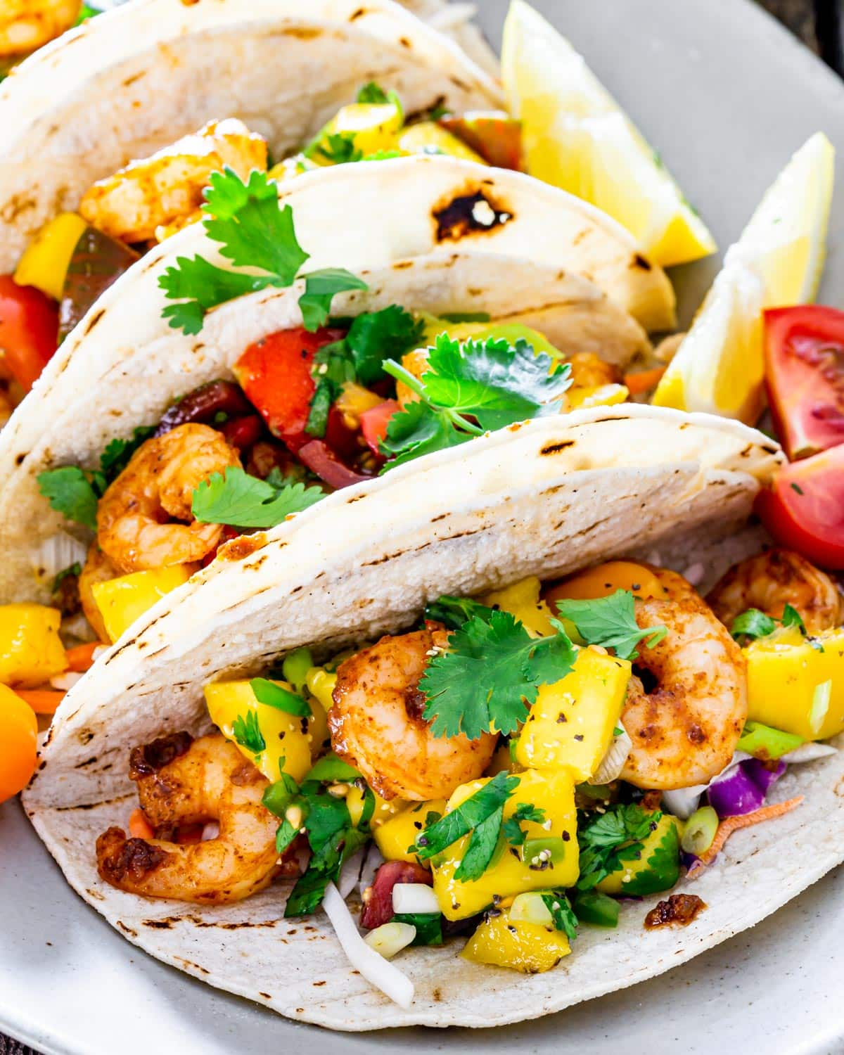 sideview shot of a plate full of cajun shrimp tacos with mango salsa