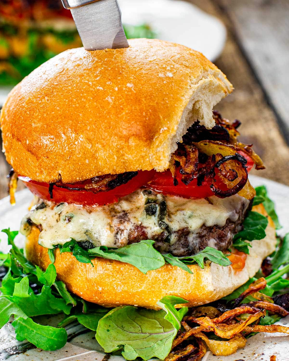 a gorgeous blue cheese burger with crispy fried onion on a plate with a knife in it