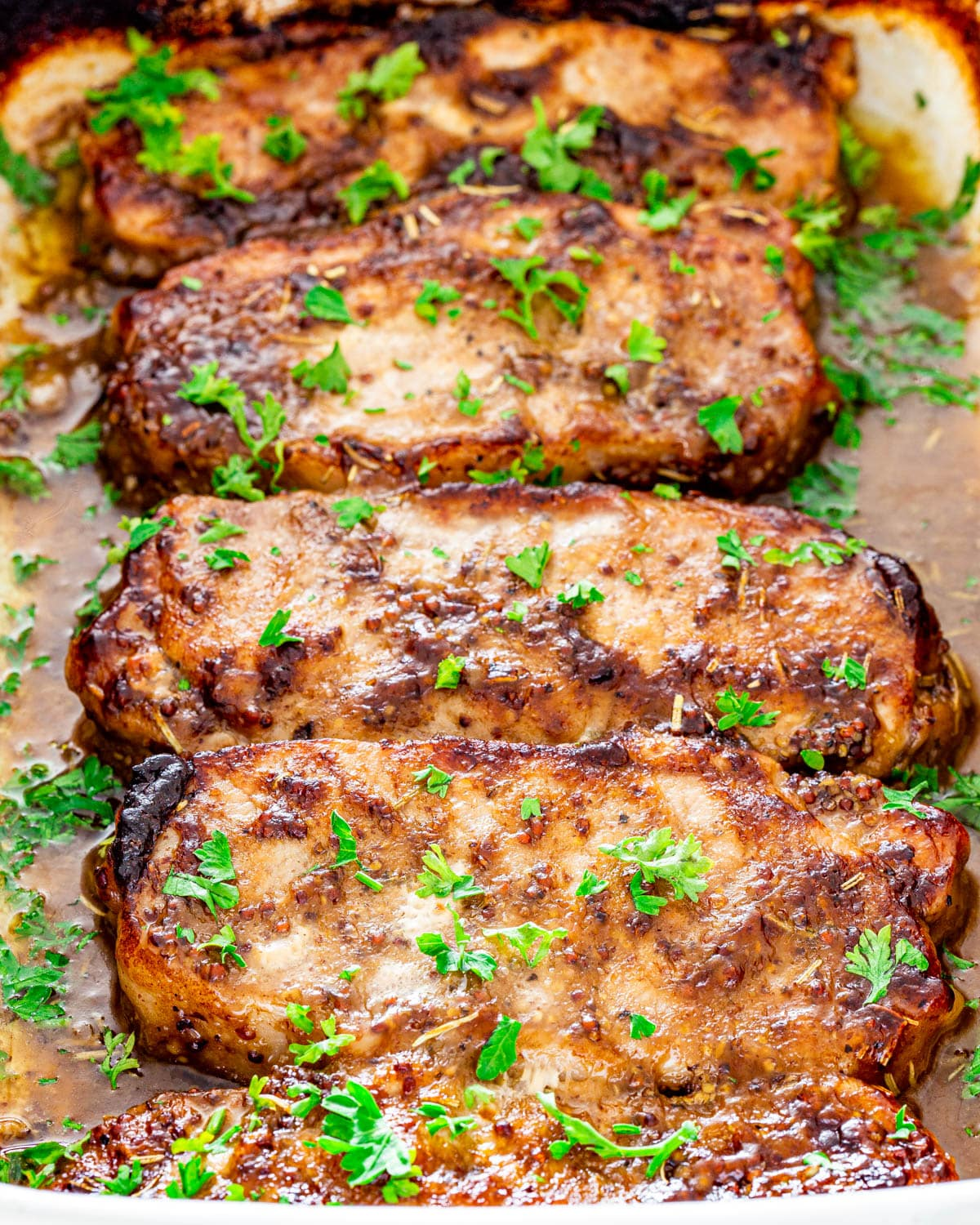 mustard balsamic pork chops in a baking dish garnished with parsley