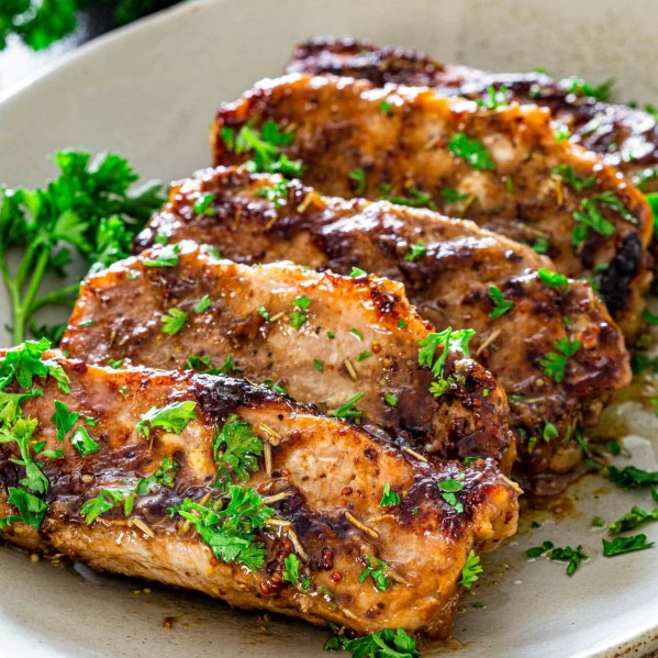 mustard balsamic pork chops lined up on a plate garnished with chopped parsley