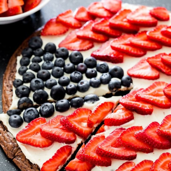 brownie pizza topped with cream cheese, fresh strawberries and blueberries to resemble the american flag