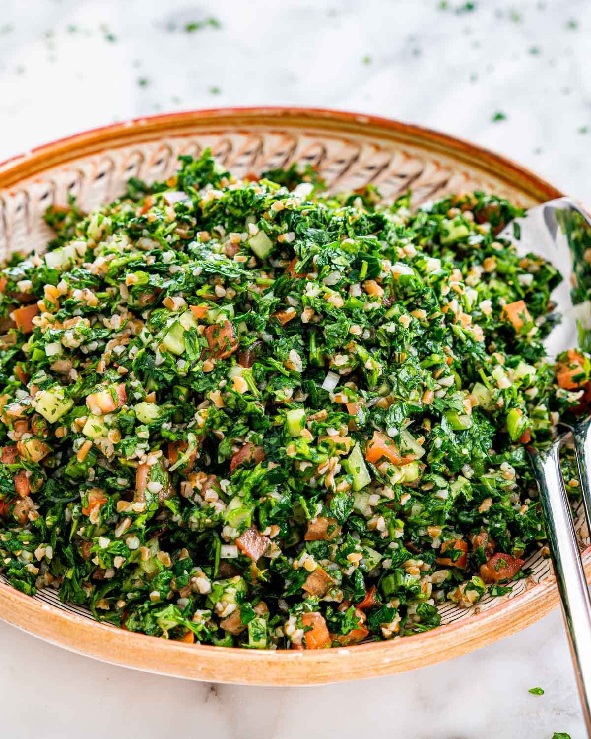 tabbouleh salad in a plate with two serving spoons in it