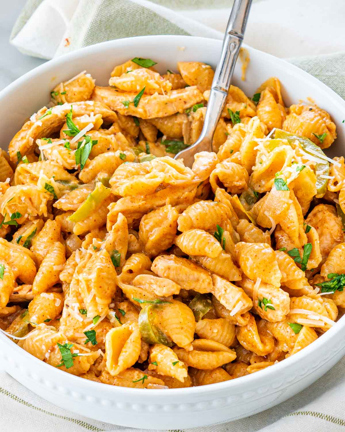 sideview shot of chicken fajita pasta in a white bowl with a fork inside