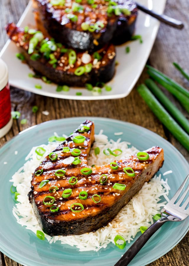 a salmon steak over a bed of rice garnished with green onions and sesame seeds