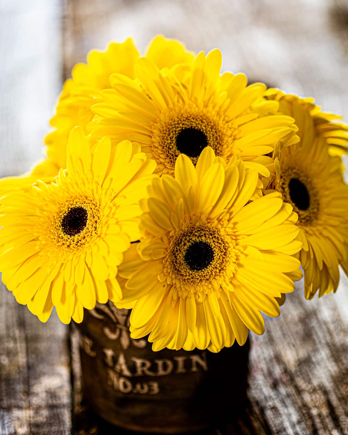 a beautiful bouquet of yellow daisies in a brown vase