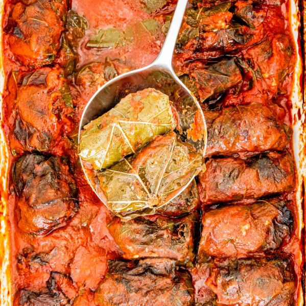 overhead shot of a serving spoon holding up two stuffed grape leaves above the pan of stuffed grape leaves