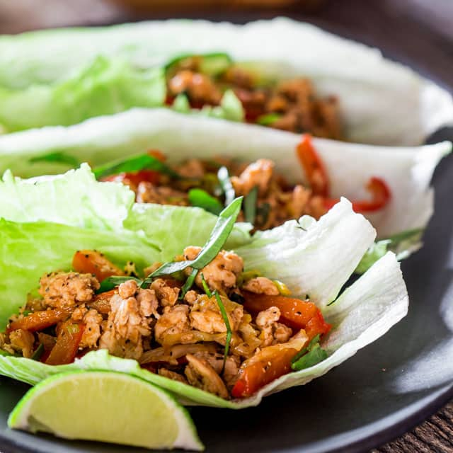 Thai Chicken Lettuce Wraps on a black plat with a lime wedge