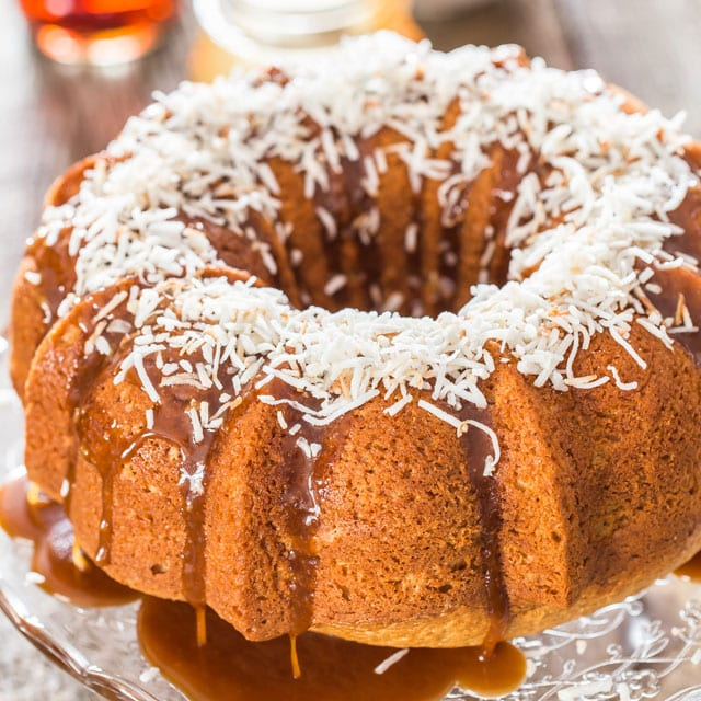 bermuda rum cake topped with caramel sauce and shredded coconut on a cake platter