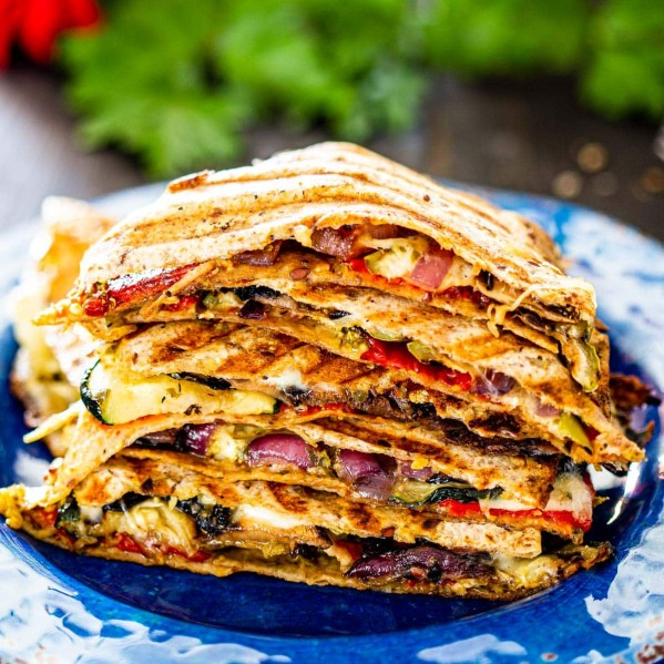 a stack of grilled vegetable quesadillas on a blue plate