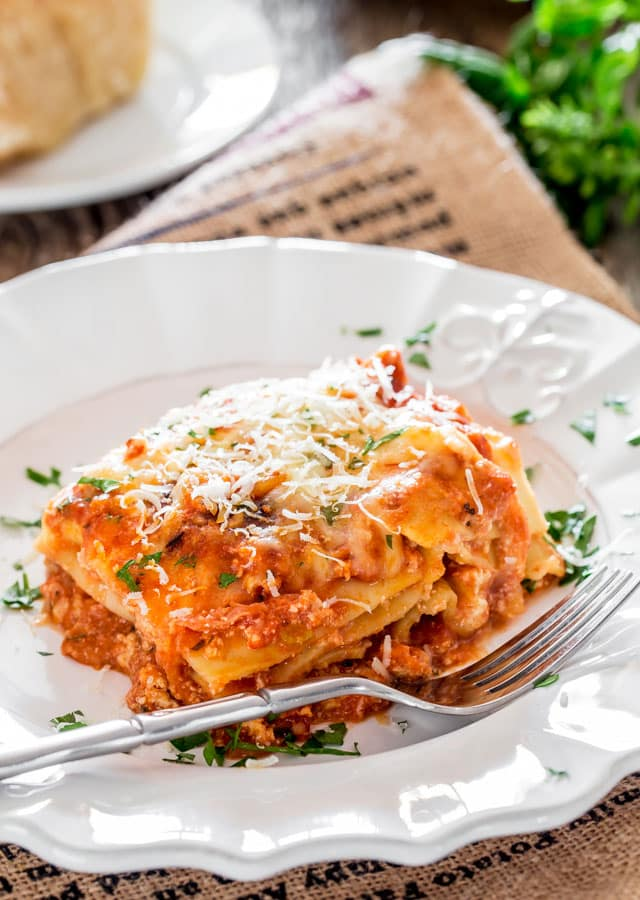 a piece of Chicken Lasagna alla Bolognese on a plate topped with parmesan and parsley