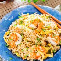 shrimp fried rice on a plate with chopsticks