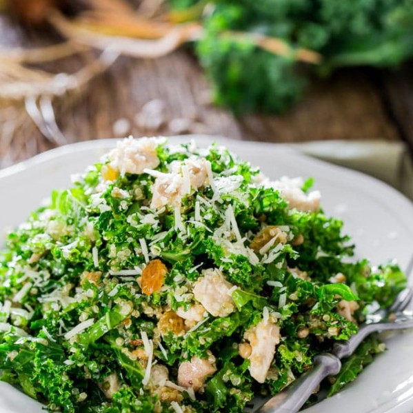 a plate of kale and quinoa salad with a fork resting on the plate